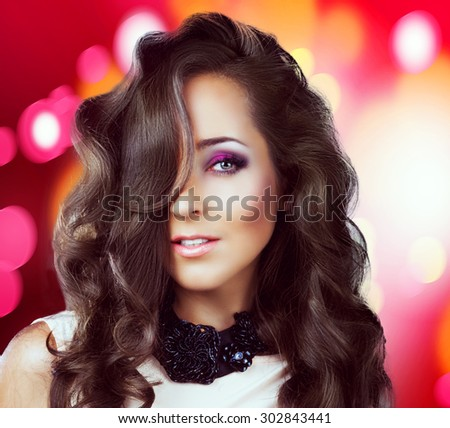 beautiful young brunette woman with long curly hair, against colorful background - stock photo