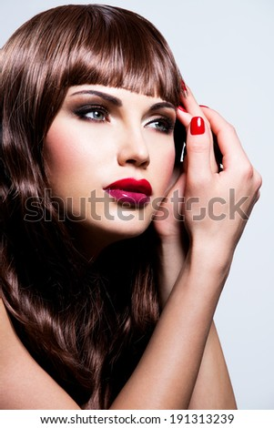 Beautiful young brunette woman with long curly hair posing at studio. Closeup portrait of a female model with fashion makeup.