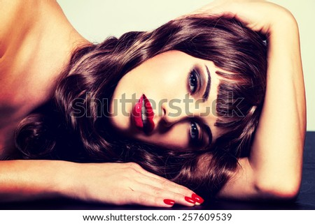 Beautiful young brunette woman with long curly hair posing at studio. Closeup portrait of a female model with fashion makeup. - stock photo