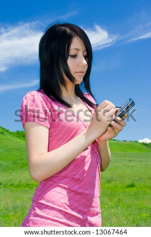 Beautiful young brunette woman with PDA outdoors - stock photo