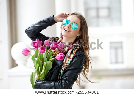 Beautiful young brunette woman with pink tulips. Woman with blue sunglasses. Smiling girl - stock photo