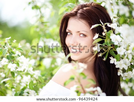 beautiful young brunette woman with the apple tree on a warm summer day - stock photo