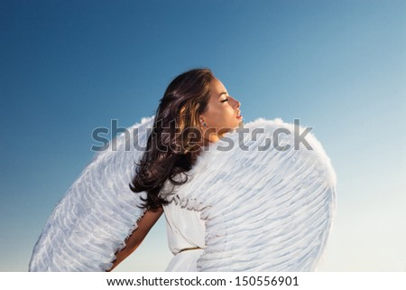 beautiful young brunette woman  with white angel wings against blue sky at sunset, profile,  back shot, small amount of grain added