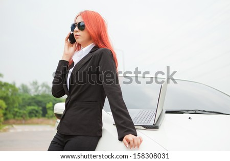 Beautiful young business asian woman using laptop and mobile phone and car - stock photo