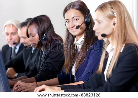 Beautiful young business customer service woman - smiling at the camera - stock photo