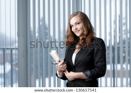 Beautiful young business girl,  with long hair, holding documents and pen in modern office. Concept image of business woman in office work.