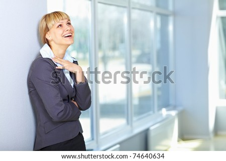 Beautiful young business lady laughing at the window - stock photo