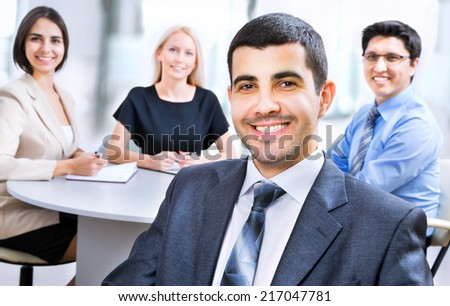 Beautiful young business man with colleagues discussing in the background