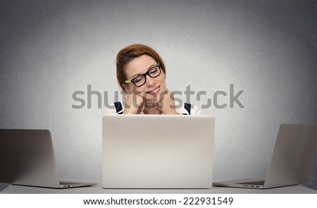 Beautiful young business woman dreaming sitting at desk working on multiple computers at her office. Positive face expression, emotion, feelings, imagination - stock photo