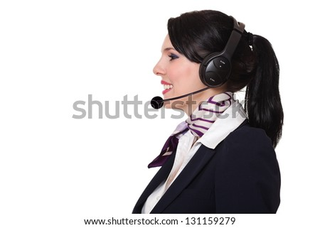 Beautiful young business woman dressed in a navy suit with a purple scarf and white shirt standing smiling and wearing earphones with microphone, looking towards left, isolated on white background - stock photo