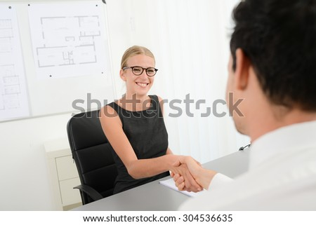 beautiful young business woman handshake with customer in office after signing agreement sales contract - stock photo