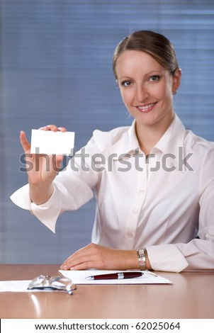 Beautiful young business woman holding a blank business card in office