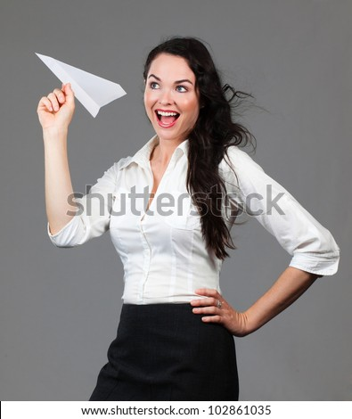 Beautiful young business woman holding a paper airplane smiling - stock photo