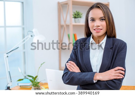 big beautiful modern office photo. beautiful young business woman in modern office with big window standing near table and photo