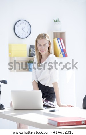 Beautiful young business woman in office - stock photo