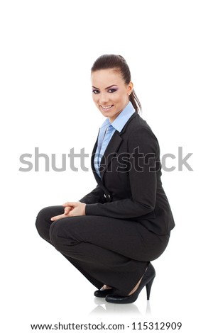 beautiful young business woman in squat position smiling while looking at the camera with her hands between her legs - stock photo