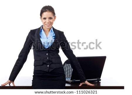 Beautiful young business woman leaning on a desk with a laptop on it. Isolated on white background. - stock photo