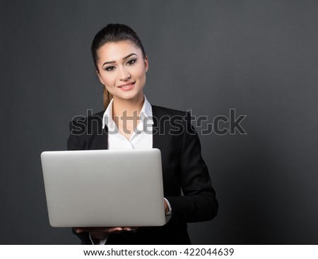 Beautiful young business woman posing with a laptop on black background
