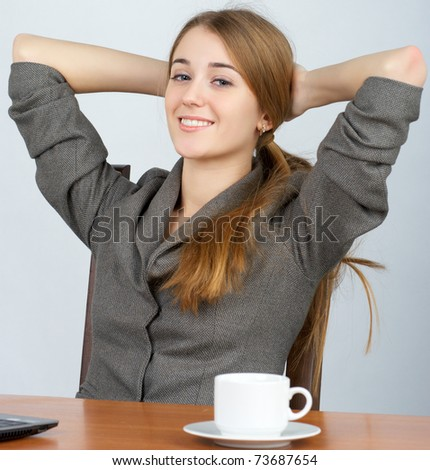 Beautiful young business woman relaxing at work with hands behind head - stock photo
