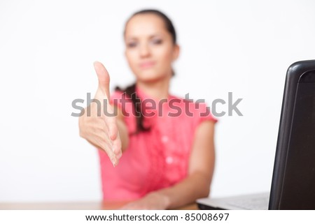 beautiful young business woman sitting at office desk and extending hand to shake - stock photo