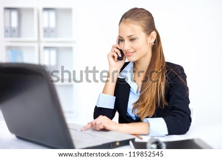 beautiful young business woman sitting at office desk and talking on cell phone - stock photo