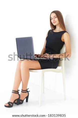 Beautiful young business woman sitting on chair working with laptop on white background - stock photo