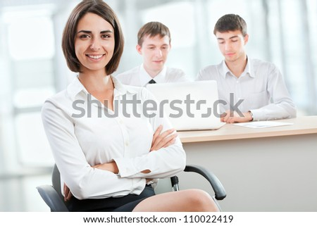 Beautiful young business woman with colleagues in the background - stock photo