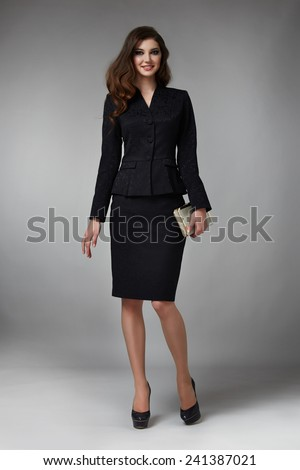 Beautiful young business woman with evening make-up wearing a black business suit skirt to the knee and jacket high heels and a small handbag, business clothes for meetings and walks autumn collection - stock photo