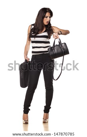 Beautiful young business woman with her ??laptop bag and ladies bag looks at her wrist watch on white background - stock photo