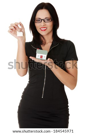 Beautiful young business woman with house construction and keys. Isolated on white. - stock photo