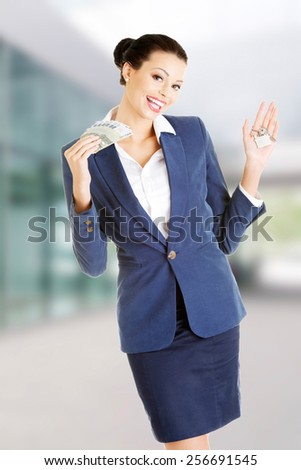 Beautiful young business woman with money and keys - stock photo