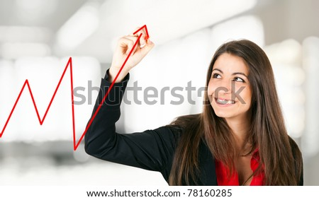 Beautiful young businesswoman drawing a red business graph - stock photo