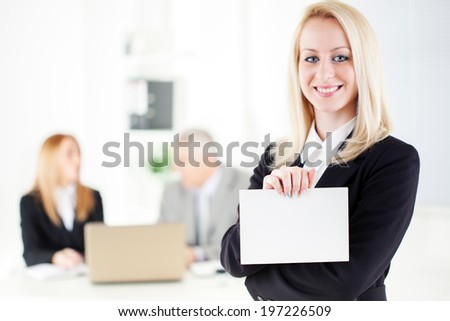 Beautiful young businesswoman holding Blank business card in the office. Looking at camera. Selective Focus. - stock photo