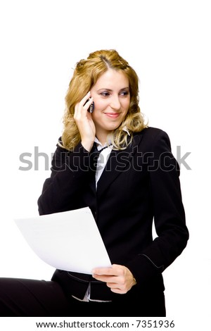 Beautiful young businesswoman is holding a blank paper in her hand while talking on the phone - stock photo