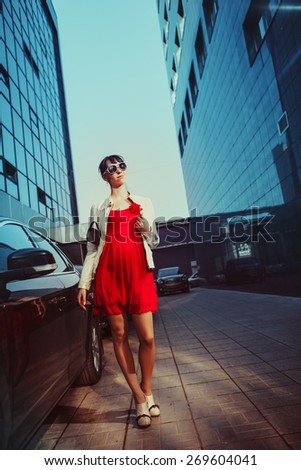 Beautiful young businesswoman is walking near skyscraper. - stock photo