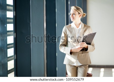 beautiful young businesswoman looking outside office window - stock photo