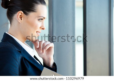 beautiful young businesswoman looking outside window - stock photo