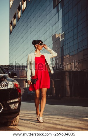 Beautiful young businesswoman near her car. Modern buildings on the background. - stock photo