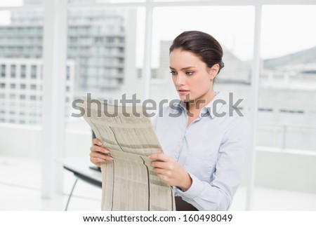Beautiful young businesswoman reading newspaper in a bright office - stock photo