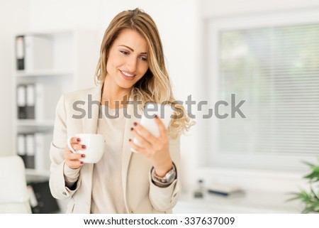 Beautiful young businesswoman relaxing in the office with coffee and using phone.