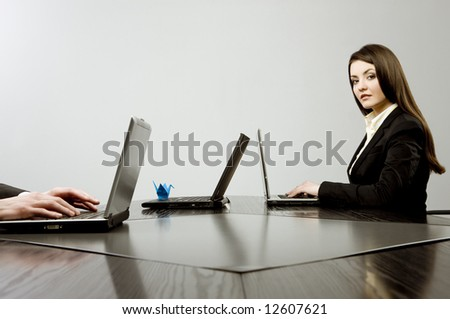 Beautiful young businesswoman sitting at a desk with three laptops with blue origami on one of them and human hands on another one - stock photo