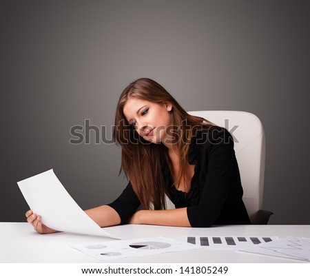 Beautiful young businesswoman sitting at desk and doing paperwork