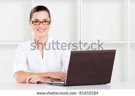 beautiful young businesswoman sitting in office with laptop - stock photo