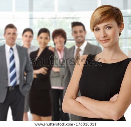 Beautiful young businesswoman smiling with business team in background. - stock photo