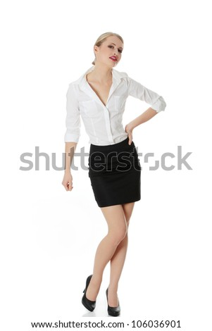 Beautiful young businesswoman standing in frivolous pose with hand on her hip. Elegant office girl in white shirt and black skirt. Isolated on the white background. - stock photo