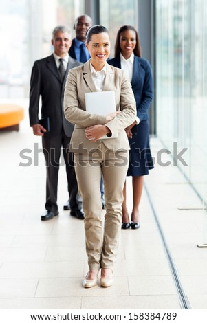 beautiful young businesswoman standing in front of colleagues - stock photo