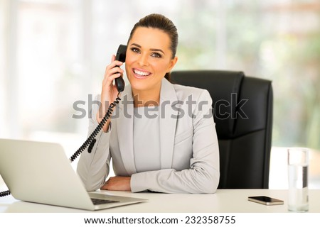 beautiful young businesswoman talking on landline phone - stock photo