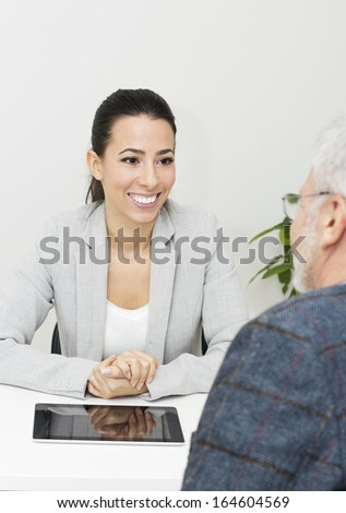 Beautiful young businesswoman talking with mature male  client. - stock photo