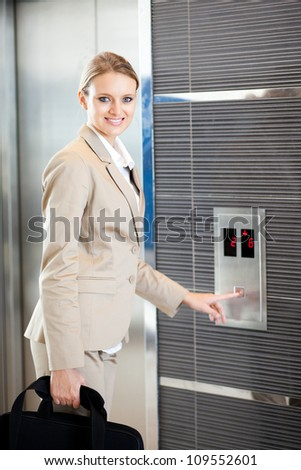 beautiful young businesswoman using elevator - stock photo