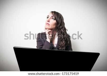 beautiful young businesswoman using notebook on gray background - stock photo